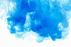 Abstract background color ink drop in water. Blue cloud of paint on white. Abstract background color ink drop in water, motion swirling. Blue cloud of paint on royalty free stock image