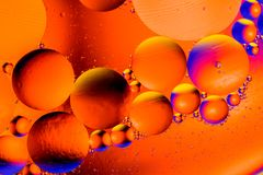Abstract background with colorful blue and orange gradient colors. Oil drops in water abstract psychedelic pattern image. stock images