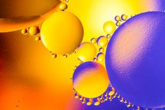 Abstract background with colorful gradient colors. Oil drops in water abstract psychedelic pattern image. Blue orange yellow color royalty free stock photos