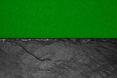 Abstract background composition of divided in the half matt dark green color paper and black stone with copy space.  stock photography