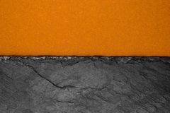 Abstract background composition of divided in the half matt dark orange color paper and black stone with copy space.  stock images