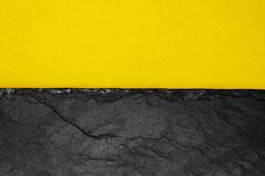 Abstract background composition of divided in the half matt dark yellow color paper and black stone with copy space.  royalty free stock photos