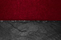 Abstract background composition of divided in the half matt vivid burgundy color paper and black stone with copy space.  royalty free stock photos