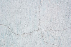 Abstract background cracked plaster surface painted white over blue Stock Photo