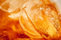 An orange gold toned backdrop created from the inside of a glass of cola with ice. stock photo