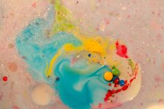 Abstract background, cyan and yellow color mix together in milk. With small color dots. Macro photo stock photo