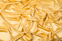 Abstract background, drapery gold fabric. Crumpled cloth, folds of fabric Stock Photography