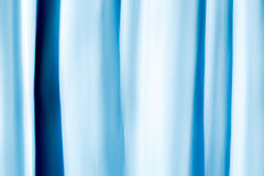 Abstract Background flowing lines of a curtain. A curtain before a window with lots of sunlight, colored with gels, shot with a longer exposure during up and Royalty Free Stock Images