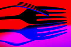 Abstract Background of Forks. Two interlocked forks and their reflection Stock Images