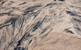 Abstract background in the form of black stains on the sand. Stock Image