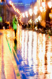 Abstract background of Girl in bright green coat. Bright reflections of street lamps in wet asphalt Intentional motion Stock Image