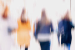 Abstract background of girls hurrying down the city street back to us. Intentional motion blur. Concept of seasons. Shopping, walking, lifestyle, modern city Royalty Free Stock Image