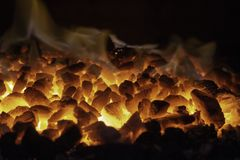 Abstract background of glowing coals in fireplace with fire flames. Burning flame background.  royalty free stock photo