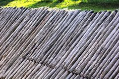 Abstract background of grey ancient wooden palisade of the protective fence on the green lawn. Stock Photo