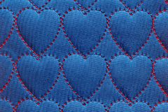Abstract background heart on textiles, red threads stitched stitches in the shape of hearts on blue cotton, denim stock photos