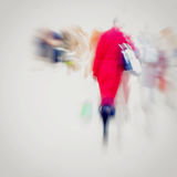 Abstract background. Intentional motion blur. Girl with handbag in red coat walking on the sidewalk. Concept of seasons. Abstract background. City in the early Royalty Free Stock Image