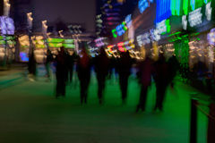 Abstract background. Intentional motion blur. Group of young people going along the street. Green shop window. Illumination. Concept of lifestyle, modern city stock image