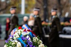 Abstract background on military theme. Flower bouquet with Estonian flag colors ribbon. A change of soldiers` guard in the royalty free stock image