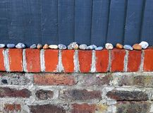 Brick wall with stones and wooden boards Stock Photos