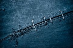 Abstract background of old tarred wooden planks of the old boat. Fastened together with Iron cramps fasteners  Tinted blue Stock Images