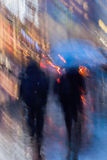 Abstract background of people hurrying down the city street in rainy evening, shop windows. Intentional motion blur Royalty Free Stock Photography