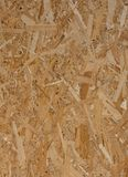 Abstract background. Pressed wooden panel, texture of oriented strand board. OSB wood. Closeup view royalty free stock image