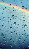 Raindrops on wet window glass and rainbow Royalty Free Stock Images