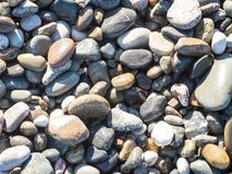 Abstract background with round peeble stones in sun light Stock Photos