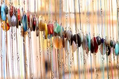 Abstract background. Samples of colorful women`s jewelry on a chain of artificial stone on bokeh background. Cropped shot, close-up, vertical, blurred. Concept royalty free stock image