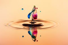 Abstract background of splash of color water, collision of colored drops. Abstract background of splash of color water, collision of orange colored drops, the stock images