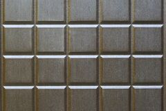 Abstract background from squares of brown color. Fragment of a metal, front door with imitation of wood. stock images