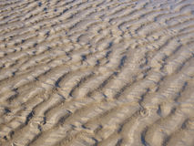 Abstract background texture of rippled sand. Abstract background texture of sand with ridged ripples formed by the action of the water in a full frame pattern Royalty Free Stock Image