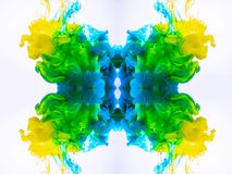 Abstract background with yellow-blue-green mystic clouds, swirling fog. Macro shot of acrylic ink blending in liquid royalty free stock photo
