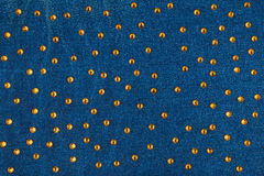 Abstract background with yellow rhinestones on denim Royalty Free Stock Images