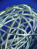 Abstract ball of silver wire. Closeup of a ball of silver wire and a blueish background Royalty Free Stock Image