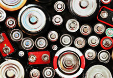 Abstract Batteries Background. The tops of batteries are shown with different sizes and charges. There is an abstract color and texture to the photo Stock Images