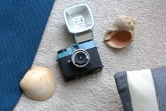 Vintage film camera, seashells and stripped cushion. Abstract beach composition with vintage film camera, seashells and stripped cushion from a high angle view stock images
