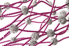 Abstract beads chain. Abstract twisted chains formed by magenta beads and wired steel balls royalty free stock photo
