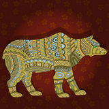 Abstract bear in the ethnic style on a maroon floral background Stock Images