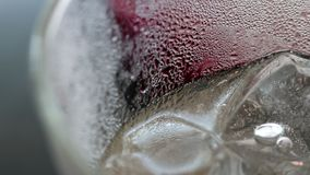 Abstract beauty in drink details. Extreme close-up of iced plum juice soda in glass. stock video footage