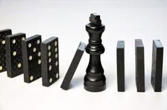 Abstract bedrijfsconcept met van de Koningsschaakstuk en domino stukken gevallen Stock Foto