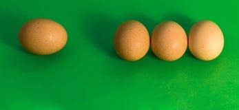 Abstract beeld in Pasen, drie eieren die dicht bij elkaar en één enkel droevig ei, op gras-groene achtergrond verder weg liggen Stock Foto