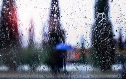 Abstract beeld van dalende regendalingen door het venster met stadsachtergrond Stock Foto's