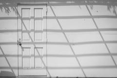 Abstract beeld van vooraanzicht witte houten deur op oude witte concrete muur met schaduw die op muur in de schaduw stellen Stock Afbeelding