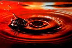 Abstract beeld van waterdaling met plons en rimpelingen op aardige rode oranje achtergrond Royalty-vrije Stock Afbeeldingen