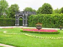 Abstract black garden arbor, flower beds and shorn trees in well. Abstract black garden arbor, flower beds and shorn trees in a well-kept park Stock Photos