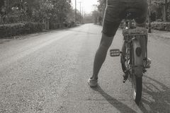 Abstract black and white image of woman sitting on old bicycle and riding on concrete road in the morning. Stock Images