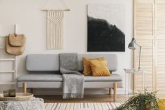 Abstract black and white painting and handmade macrame on white wall of natural living room interior with grey fashionable couch stock images