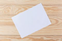 Abstract Blank one white paper on wooden table top view background concept for empty letter business sheet, plain brochure mock up. Template, flyer card stock photo