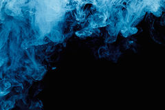 Abstract blue cloud pattern of white smoke on a black background. Stock Photo